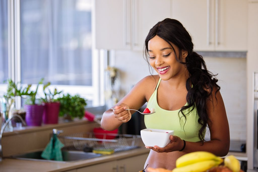 woman smiling and starting to eat breakfast from the Eating for Happiness custom diet program
