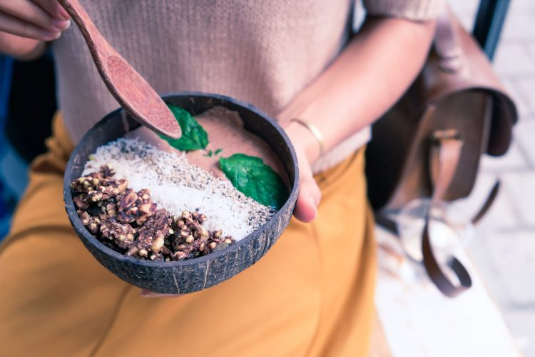 Woman enjoying a delicious smoothie bowl - whole-some plant based diet