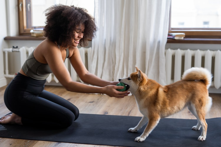 Happy woman playing with her dog on her gym mat