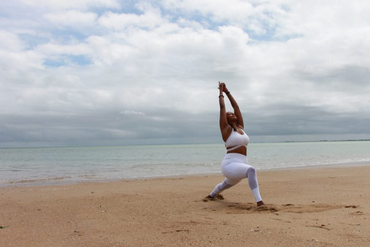 Beautiful middle aged woman doing yoga yoga on the beach in white sport gears